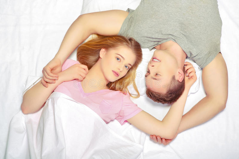 Beautiful young couple in bed stock photography