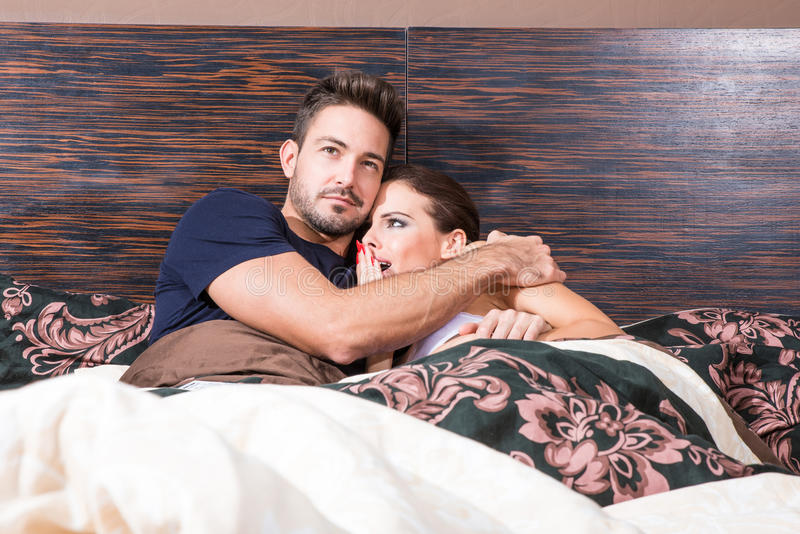 Beautiful young couple being scared in bed stock images