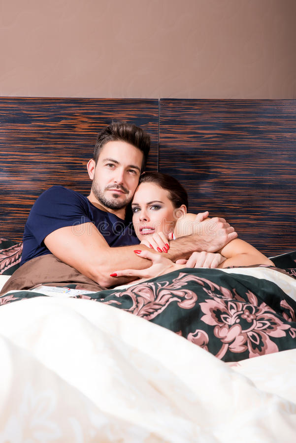 Beautiful young couple being scared in bed royalty free stock images