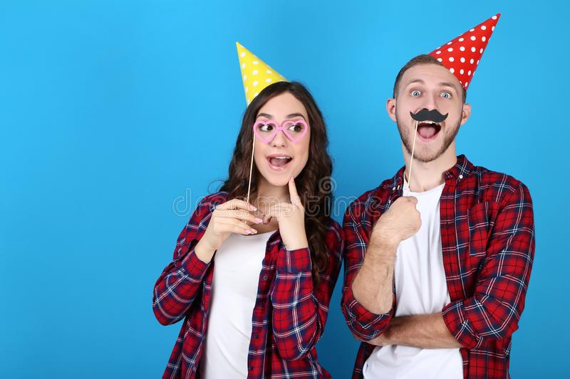 Young couple in birthday caps and booth props. Beautiful young couple in birthday caps and paper booth props on blue background stock images