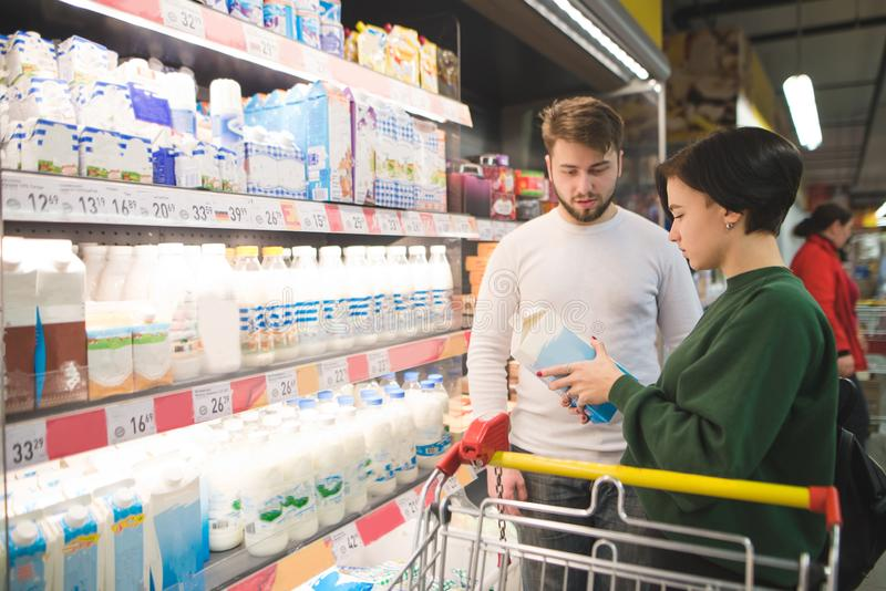 A beautiful young couple chooses dairy products in a supermarket. The girl reads the milk ethics in the store royalty free stock image