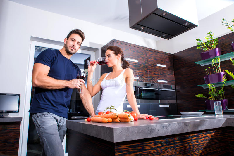 Beautiful young couple cooking while drinking wine in the kitchen royalty free stock photography