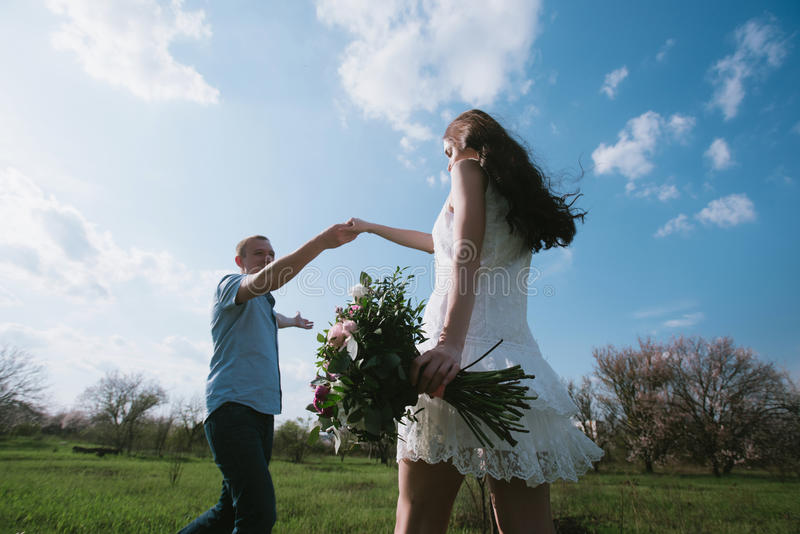 Beautiful young couple dancing and having fun on blue sky background stock photo