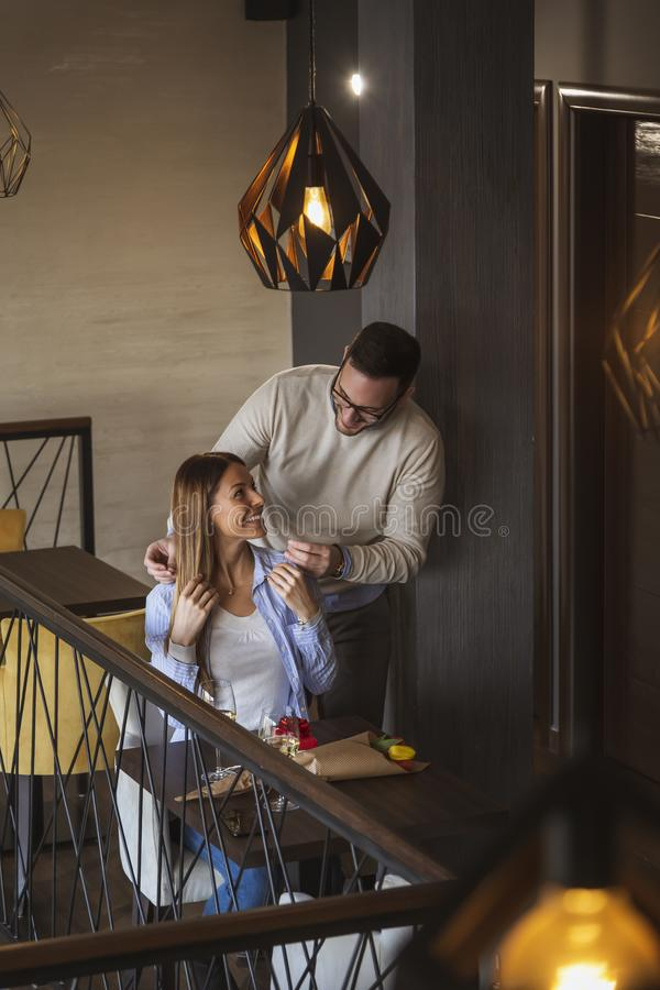 Man attaching necklace around woman`s neck royalty free stock photos