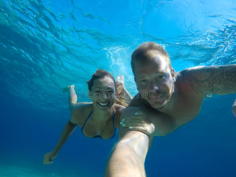 Beautiful young couple diving in the ocean royalty free stock photo