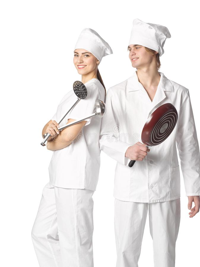 Beautiful young couple dressed in cooks with cooking tools stand stock photography