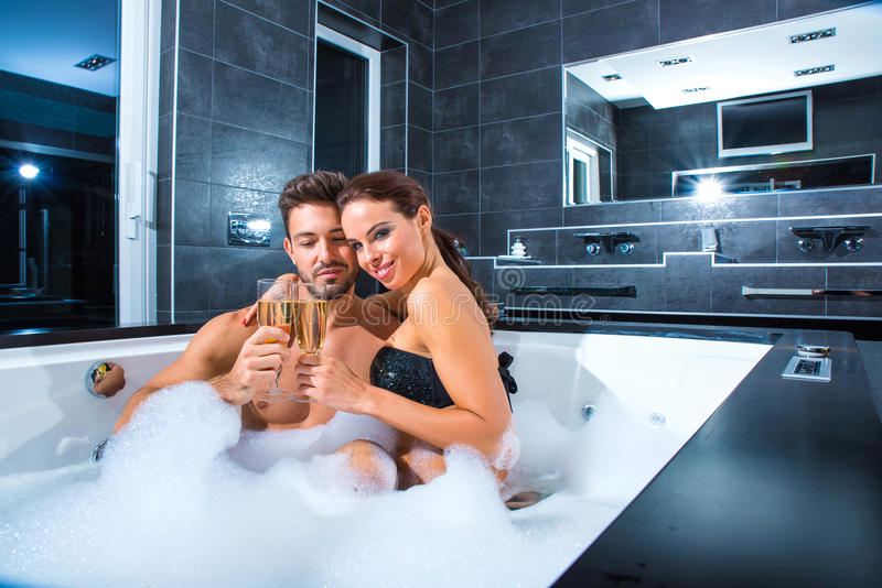 Beautiful young couple drinking Champagne in the Whirlpool. Beautiful young couple relaxing together and drinking Champagne in the Whirlpool royalty free stock images