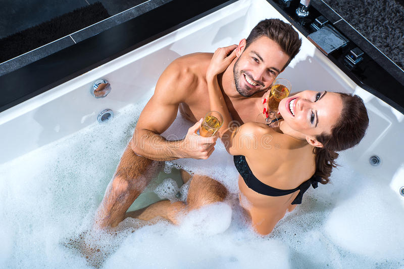 Beautiful young couple drinking Champagne in the Whirlpool royalty free stock photos
