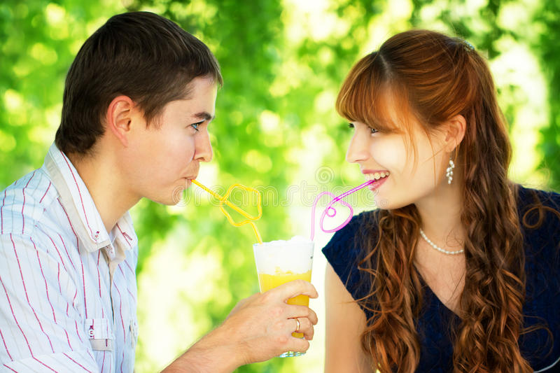 Beautiful Young Couple Drinking Juice from one Glass with Colored Tubes. Picnic in Countryside. Happy Family Outdoor. Smiling Man royalty free stock photos