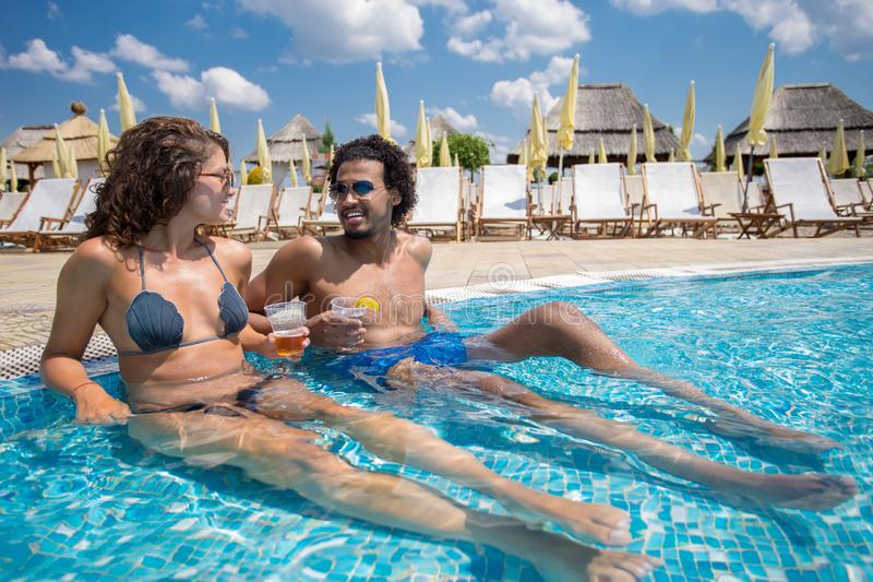 Beautiful young couple enjoying a vacation day at the pool royalty free stock photography