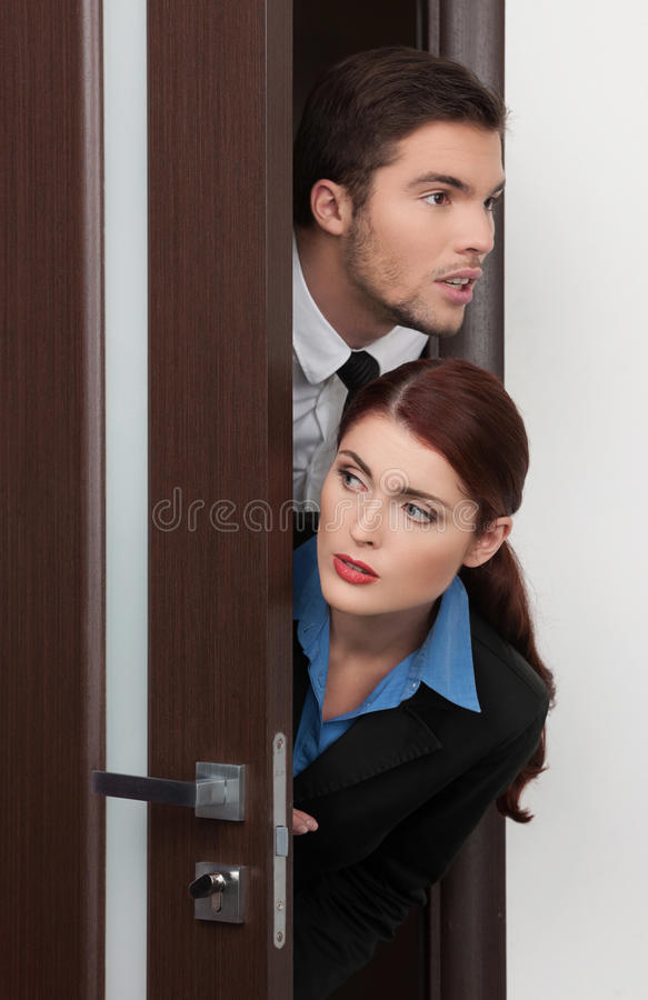 Beautiful young couple entering room. Handsome and pretty women opens door stock photography