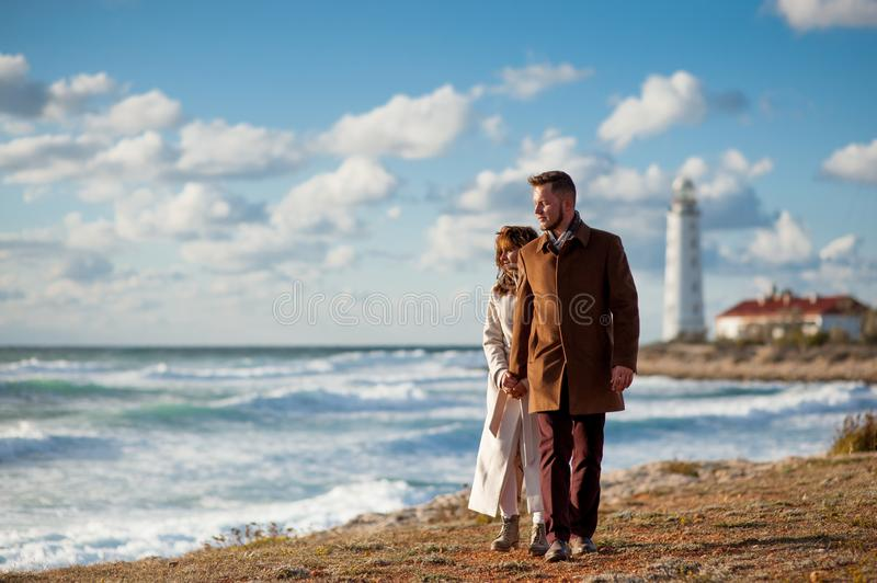 Beautiful young couple family bearded nordic man and trendy female in coat walking along sea shore with lighthouse hand in hand in royalty free stock image