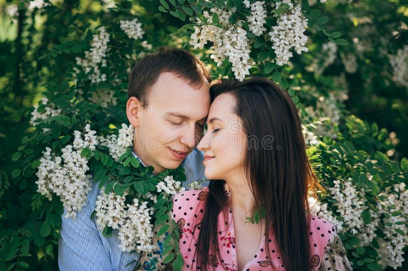 Beautiful young couple gently hugging in green leaves and white flowers in spring garden in sunshine. Happy family embracing at royalty free stock photos