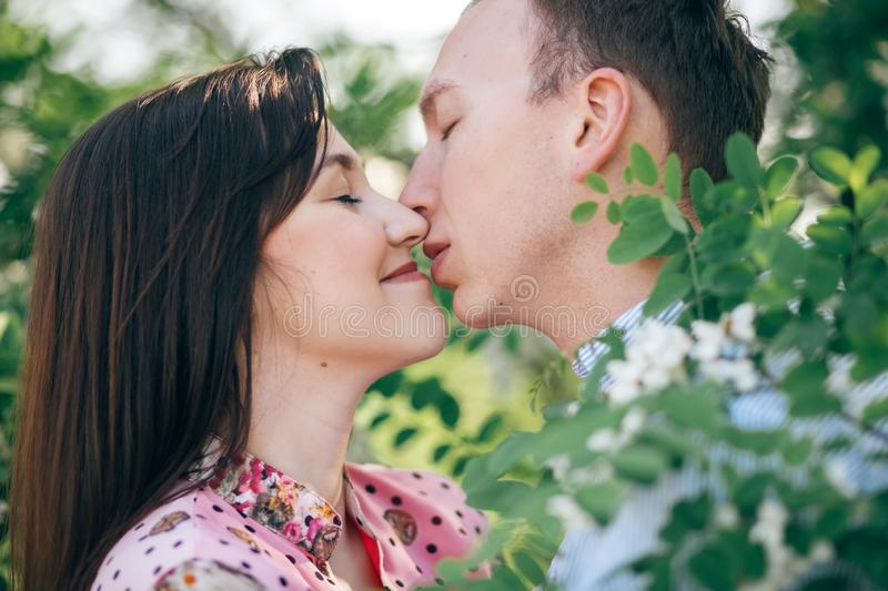 Beautiful young couple gently hugging and kissing at green leaves and white flowers in spring garden. Happy family embracing at stock photos