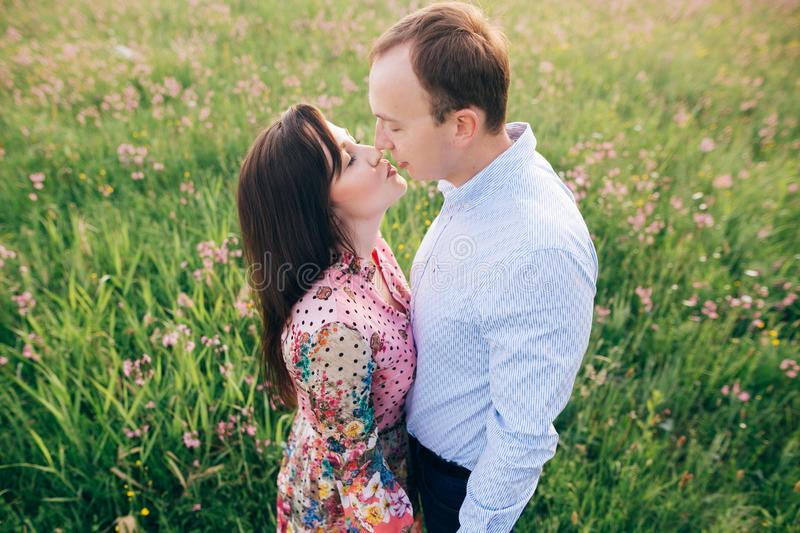 Beautiful young couple gently hugging and kissing in sunshine in fresh spring meadow with pink flowers. Happy stylish family royalty free stock image