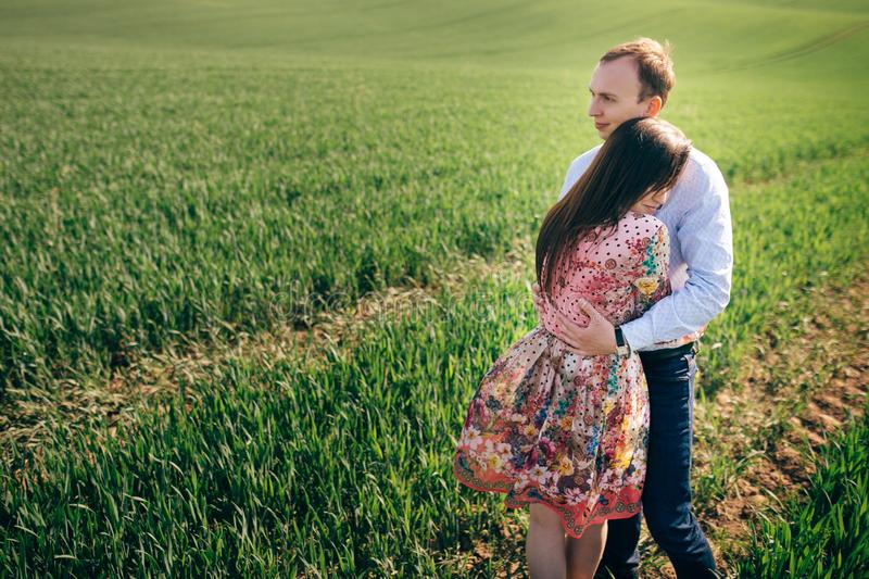 Beautiful young couple gently hugging in sunshine in spring green field. Happy family embracing in green meadow with fresh grass royalty free stock photo
