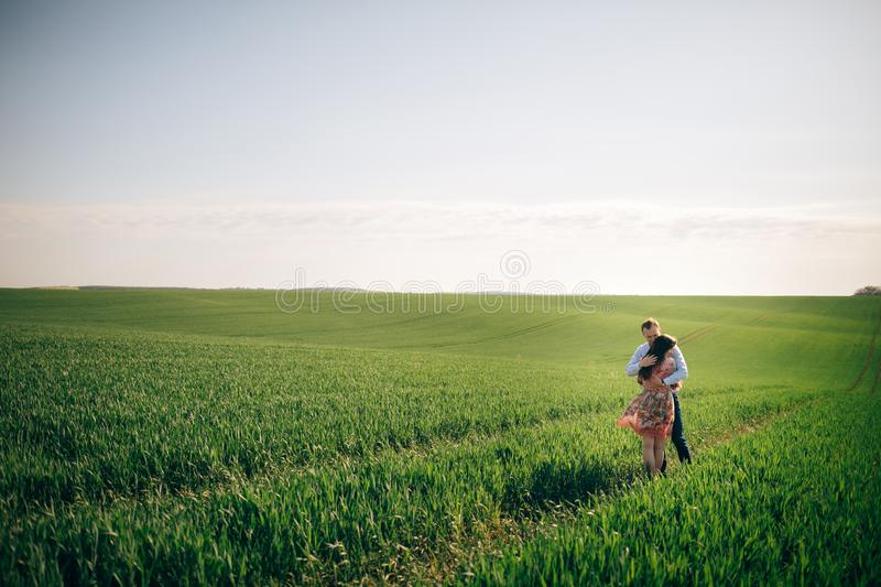 Beautiful young couple gently hugging in sunshine in spring green field. Happy family embracing in green meadow with fresh grass stock photo