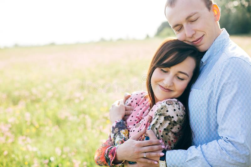 Beautiful young couple gently hugging in sunshine in spring meadow. Happy stylish family embracing in green field with flowers. stock photo