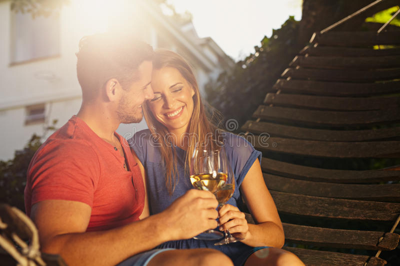 Beautiful young couple on hammock toasting wine. Beautiful young couple toasting wine outdoors. They are sitting on a hammock smiling and drinking wine with stock photography