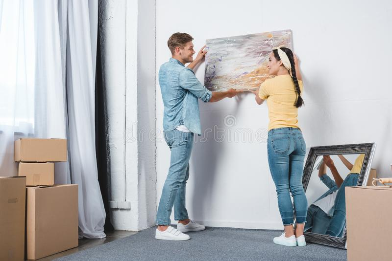 beautiful young couple hanging picture on wall together while moving into royalty free stock images