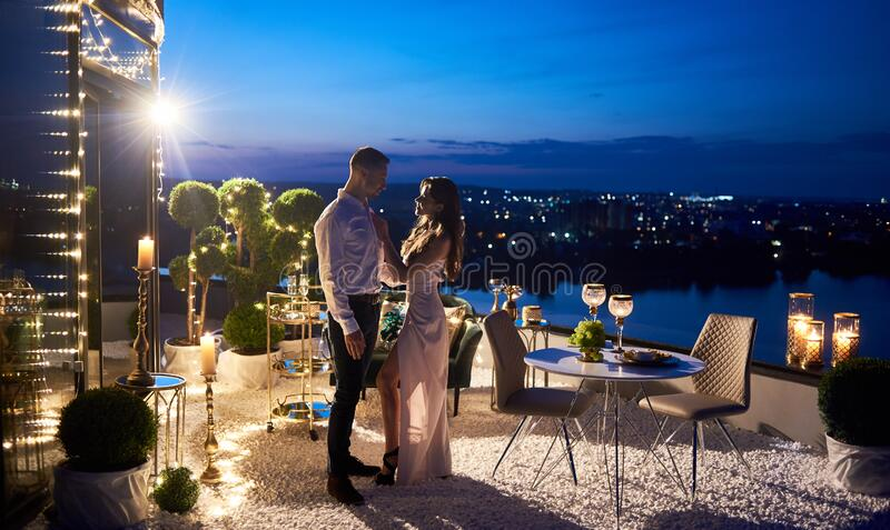 Beautiful young couple having date at rooftop restaurant. royalty free stock photography