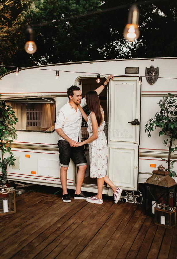 Beautiful young couple having fun, young people near their mobile home stock photo
