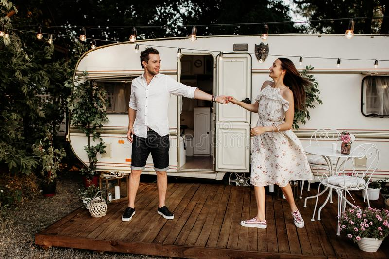 Beautiful young couple having fun, young people near their mobile home royalty free stock photography