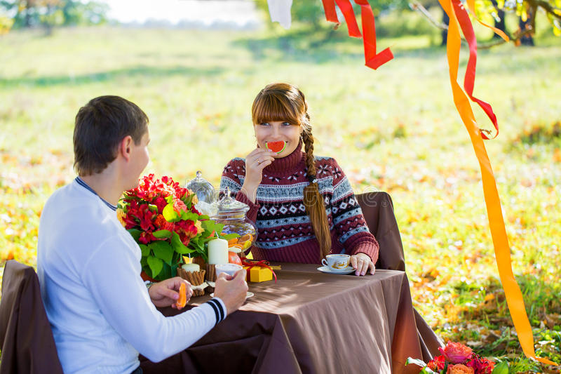 Beautiful Young Couple Having Picnic in autumn Park. Happy Family Outdoor. Smiling Man and Woman relaxing in Park. Relationships. stock photos
