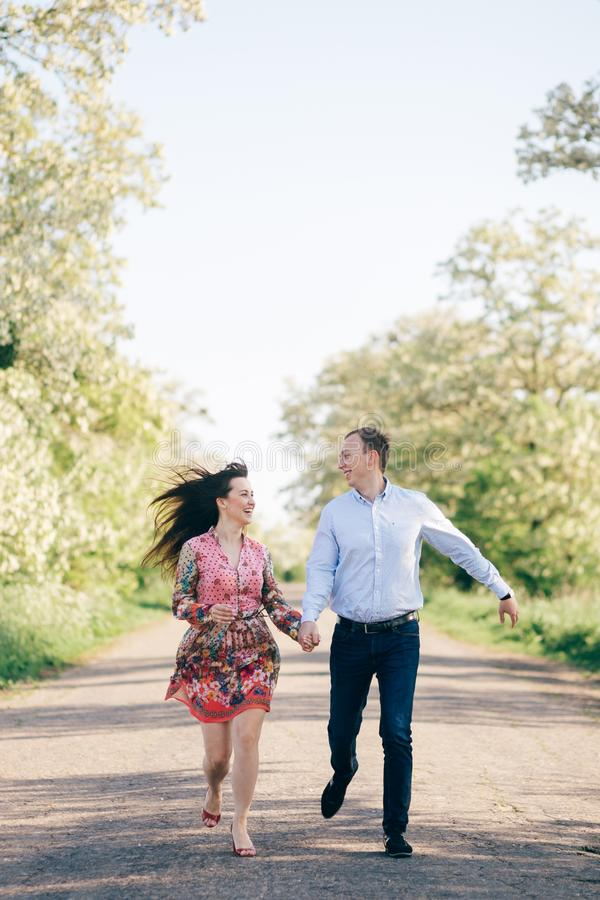 Beautiful young couple holding hands and running on road in sunshine among spring field and trees. Happy family in love having fun stock images