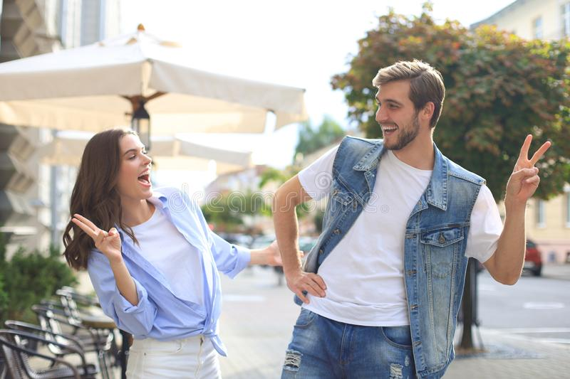 Beautiful young couple holding hands and smiling while walking through the city street. royalty free stock image