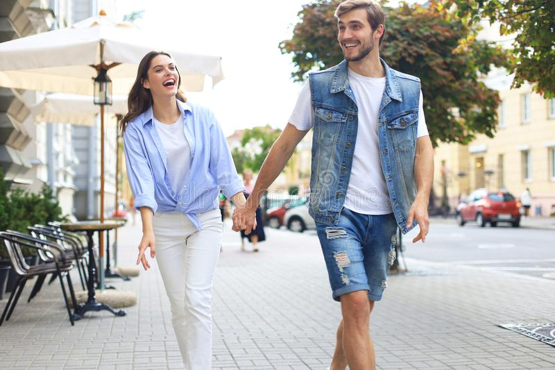 Beautiful young couple holding hands and smiling while walking through the city street. stock images