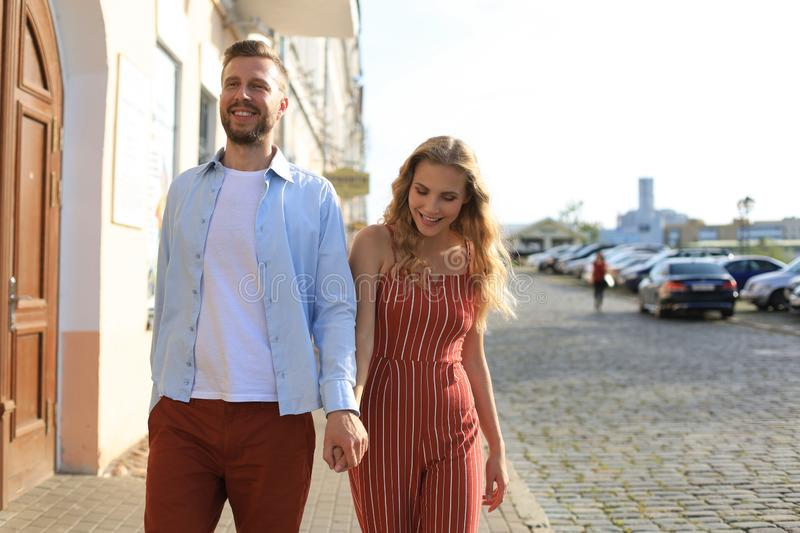 Beautiful young couple holding hands and smiling while walking through the city street royalty free stock image