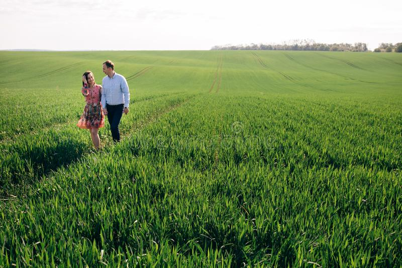 Beautiful young couple holding hands and walking in sunshine in spring meadow. Happy family embracing in green field in sunlight. Romantic moments. Valentine stock images