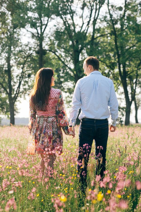 Beautiful young couple holding hands and walking in sunshine in spring meadow with pink flowers. Happy family smiling in green stock images