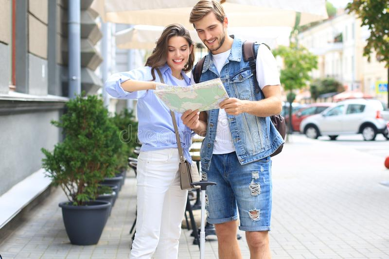 Beautiful young couple holding a map and smiling while standing outdoors. stock image
