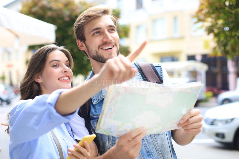 Beautiful young couple holding a map and smiling while standing outdoors. stock images