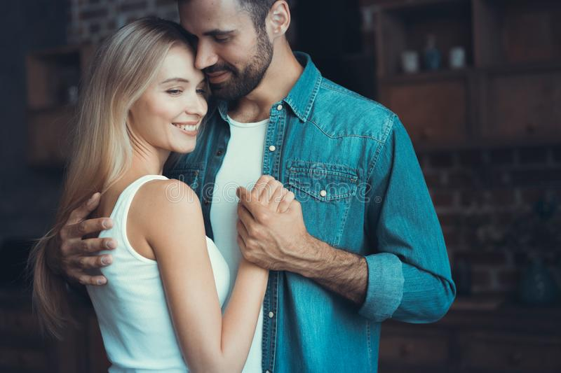 Beautiful young couple hugging in their new appartment royalty free stock image