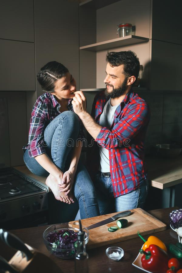 Beautiful young couple in kitchen at home while cooking healthy food. Husband cuts salad and feeds his wife cucumber. Scene from royalty free stock image