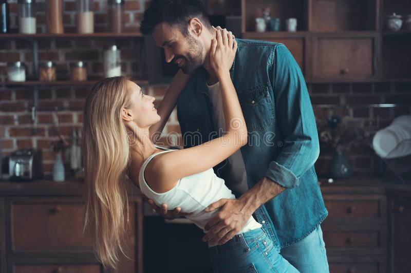 Beautiful young couple is looking at each other and smiling while dancing in kitchen. stock photos