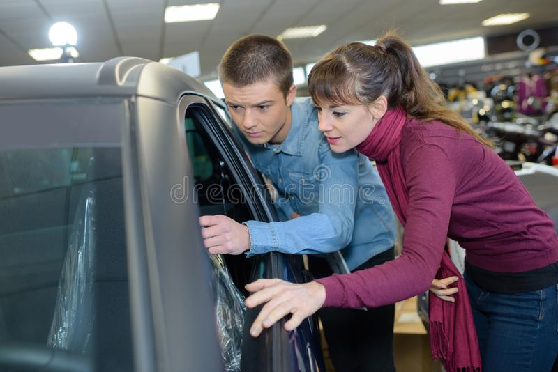 Beautiful young couple looking for new car at car dealer stock image