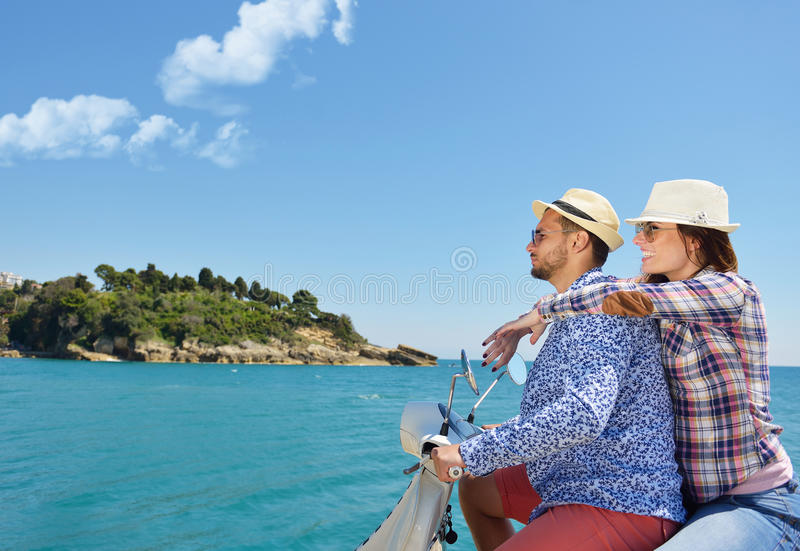Beautiful young couple in love enjoying and having fun riding on a scooter in a beautiful nature.  stock images