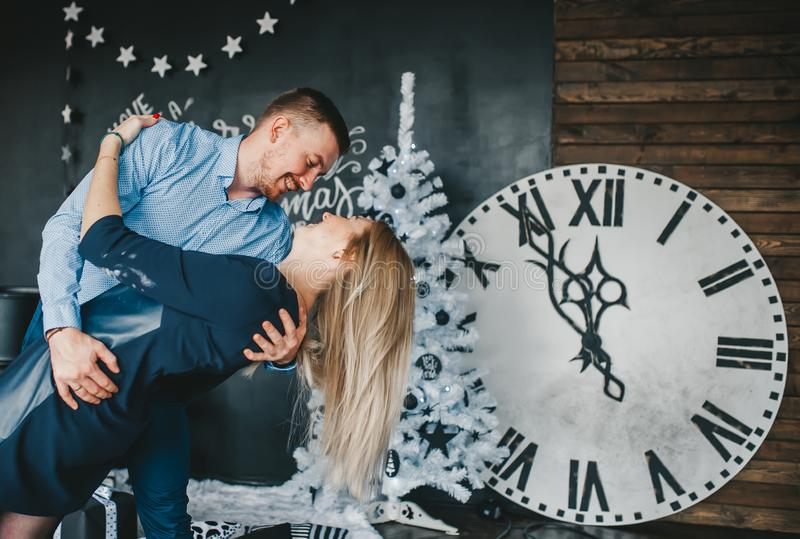 Beautiful, young couple in love hugging and dancing a midnight tango against the background of the wall clock royalty free stock photo