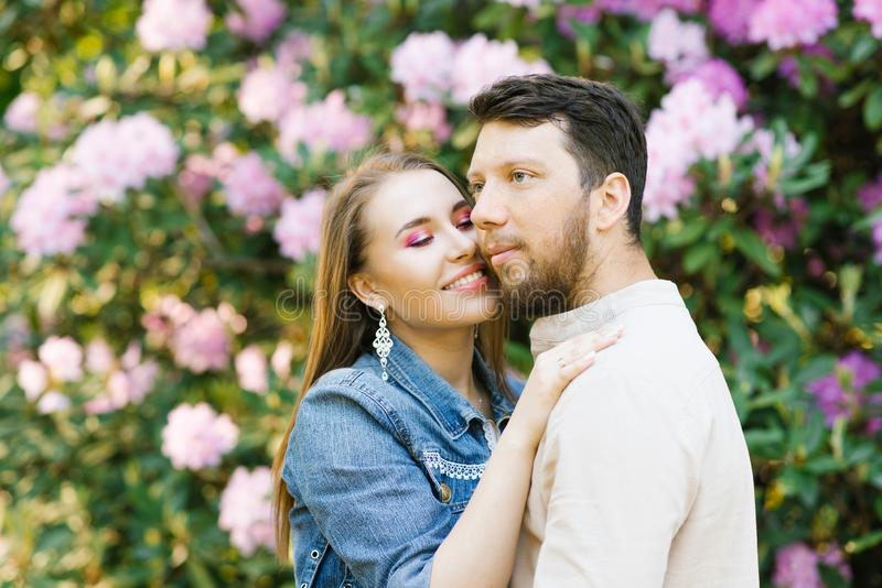 Beautiful young couple in love husband and wife hug each other, enjoying the spring summer day, walking in the Park. Happy and har. Monious relationship stock photography