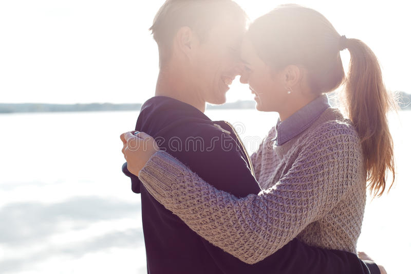 Beautiful young couple in love walking on the shore of the lake at sunset in the rays of bright light stock image