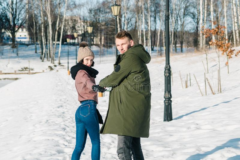 Beautiful young couple in love walks in the park on a clear sunny winter day royalty free stock photography