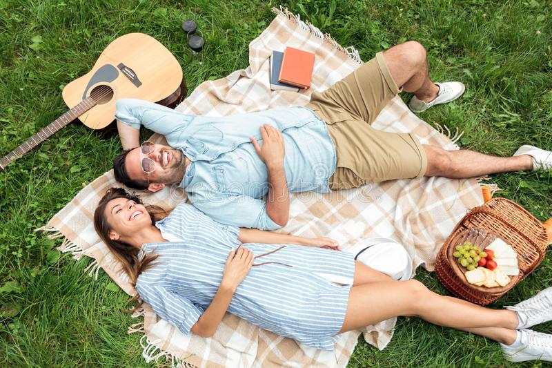 Beautiful young couple lying next to each-other and relaxing on a picnic blanket, enjoying their day away from urban life. High angle view. Love, dating stock photos