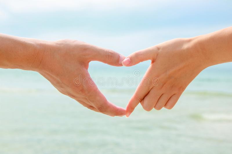 Beautiful young couple is making heart with the fingers royalty free stock image