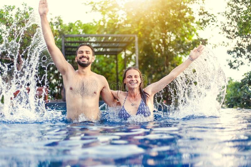 Beautiful young couple man and woman having fun in the outdoor p. Beautiful young couple men and women having fun in the outdoor pool, splash, vacation and royalty free stock photo