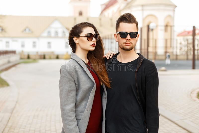 Beautiful young couple models in fashionable clothes posing outdoors. royalty free stock images