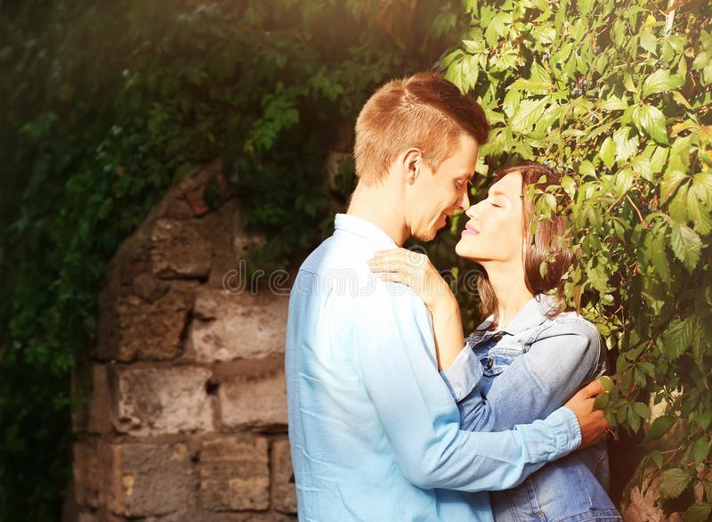 Beautiful young couple outdoors near old wall stock photo